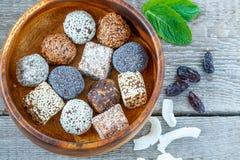 Boules crues saines d'énergie avec du cacao, noix de coco, sésame, chia dans une cuvette en bois Photos libres de droits