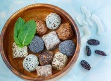 Boules crues saines d'énergie avec du cacao, noix de coco, sésame, chia dans une cuvette en bois Image libre de droits