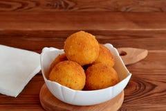 Boules d'Arancini d'un plat Recette de côtelettes de riz frit Fond en bois de Brown Photos libres de droits