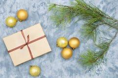 Boules d'or de Noël, boîte-cadeau avec l'arc et branche impeccable sur un fond concret photo stock
