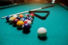 Boules de billard dans une table de billard à la triangle avec la queue de billard Images stock
