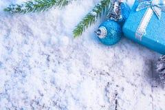 Boules de boîte-cadeau, cônes de pin et branche verte sur la neige Photographie stock