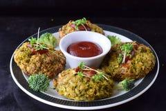 Boules de brocoli cuites à la friteuse d'un plat blanc avec la sauce tomate avec le brocoli frais sur un fond abstrait noir Sain images stock