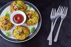 Boules de brocoli cuites à la friteuse d'un plat blanc avec la sauce tomate avec le brocoli frais sur un fond abstrait noir Sain photo stock