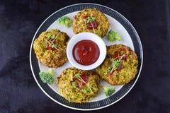 Boules de brocoli cuites à la friteuse d'un plat blanc avec la sauce tomate avec le brocoli frais sur un fond abstrait noir Sain photos stock