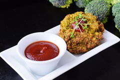 Boules de brocoli cuites à la friteuse d'un plat blanc avec la sauce tomate avec le brocoli frais sur un fond abstrait noir Sain photo libre de droits