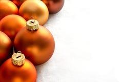Boules de couleur orange en bronze de chtristmas de tapis sur un fond blanc photos stock