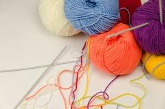Boules de fil coloré, aiguilles de tricotage Photographie stock