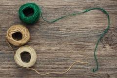 Boules de fil dans la couleur verte et beige sur une surface en bois Fil de toile dans un embrouillement La vue à partir du dessu Images stock