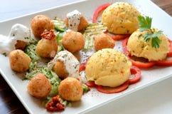 Boules de fromage avec la purée de pommes de terre d'un plat blanc photo stock