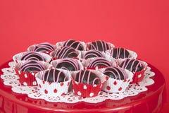 Boules de gâteau de chocolat dans les revêtements rouges et blancs de point du plat rouge Photo stock