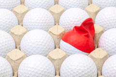 Boules de golf blanches dans la boîte pour des oeufs Boule de golf avec le chapeau drôle Images libres de droits