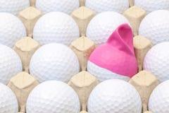 Boules de golf blanches dans la boîte pour des oeufs Boule de golf avec le chapeau drôle Image stock