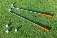 Boules de golf et clubs de golf sur l'herbe Images stock