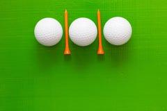 Boules de golf et tees de golf en bois sur la table verte Images stock