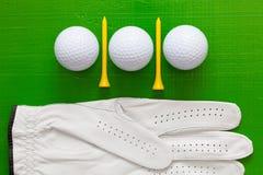 Boules de golf et tees de golf en bois sur la table verte Photo stock