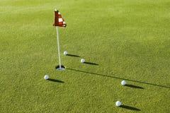 Boules de golf par le drapeau sur le cours Photo stock