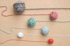Boules de la laine de diverses couleurs avec les brins de remorquage Photographie stock