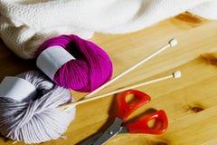 Boules de laine et d'aiguilles de tricotage en bois sur la table Photo libre de droits