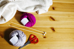 Boules de laine et d'aiguilles de tricotage en bois sur la table Photographie stock libre de droits