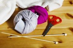 Boules de laine et d'aiguilles de tricotage en bois sur la table Image stock