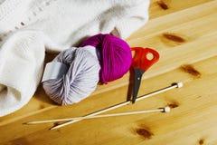 Boules de laine et d'aiguilles de tricotage en bois sur la table Photographie stock