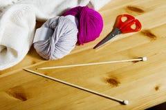 Boules de laine et d'aiguilles de tricotage en bois sur la table Photos stock