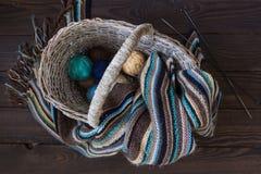 Boules de laine tricotées d'écharpe et de fil dans un panier en osier sur un bois Photographie stock libre de droits