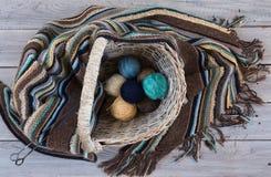 Boules de laine tricotées d'écharpe et de fil dans un panier en osier sur un bois Images stock