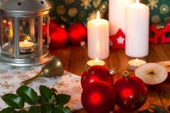 Boules de Noël avec la lanterne, les bougies, la pomme et la cloche Photographie stock