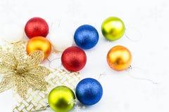 Boules de Noël avec le ruban d'or de fleur et flocons de neige sur le fond blanc Photographie stock libre de droits