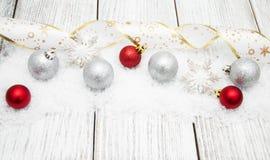 Boules de Noël avec le ruban sur la neige Photographie stock