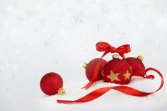 4 boules de Noël avec le ruban tombant vers le bas neige se tient le premier rôle Image libre de droits