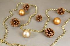 Boules de Noël, cônes de pin et tresse de perles Photos stock