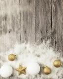 Boules de Noël d'or, boules de neige, neige d'hiver et étoile éclatantes sur le fond en bois Photos libres de droits