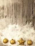 Boules de Noël d'or, boules de neige, neige d'hiver et étoile éclatantes sur le fond en bois Photo libre de droits