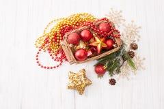 Boules de Noël dans un panier en osier sur un fond blanc Image stock