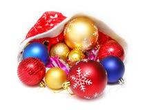 Boules de Noël, jouets dans le chapeau rouge de Santa Claus Photographie stock libre de droits