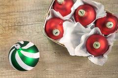 Boules de Noël rouges et vertes dans une vue supérieure de panier en bois de vin Image stock
