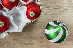 Boules de Noël rouges et vertes dans une vue supérieure de panier en bois de vin Photographie stock libre de droits