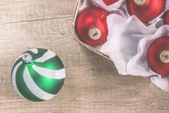 Boules de Noël rouges et vertes dans une vue supérieure de panier en bois de vin Photos stock