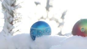 Boules de Noël sur la branche couverte de neige de sapin banque de vidéos