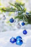 Boules de Noël sur la neige et la branche de l'arbre de Noël extérieures Photo stock