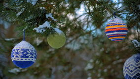 Boules de Noël accrochant sur des branches de pin couvertes de neige banque de vidéos