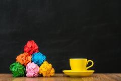 Boules de papier coloré de déchets avec une tasse jaune Image stock