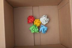 Boules de papier colorées chiffonnées à l'intérieur de boîte en carton Image libre de droits