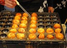 Boules de rotation de poulpe de takoyaki de chef sur le gril, Osaka, Japon Image stock