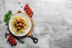 Boules de spaghetti et de viande d'un plat avec des tomates, des herbes et l'ail photographie stock