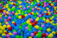 Boules en plastique colorées dans la piscine de la pièce de jeu photographie stock libre de droits