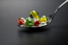 Boules en verre colorées dans une cuillère en métal Photo libre de droits